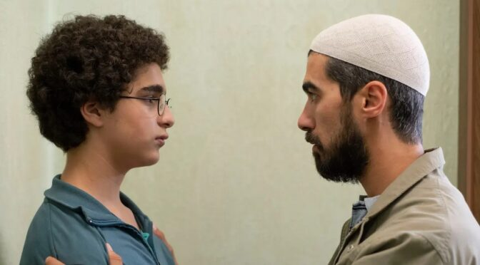 A young boy with glasses and curly hair looks into the eyes of an older man wearing kufi Islamic headwear