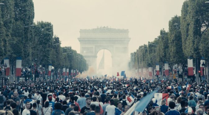 An enormous crowd gathered in front of Paris's monument, the Arc de Triomphe, celebrating France's World Cup win by waving flags